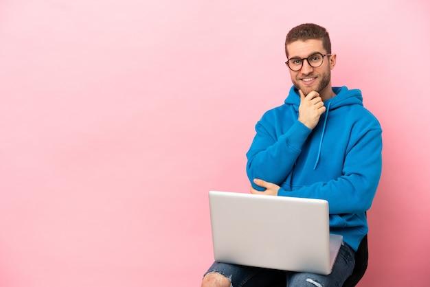 Giovane uomo seduto su una sedia con laptop con occhiali e sorridente