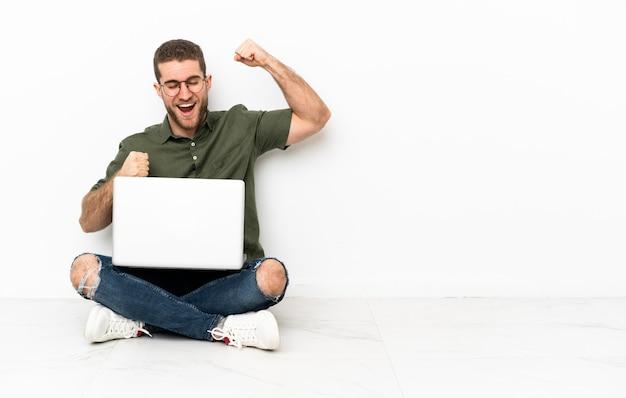 Giovane uomo seduto sul pavimento che celebra una vittoria