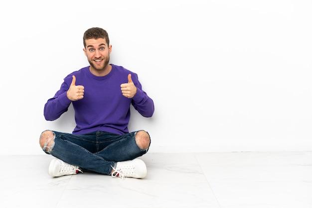 Giovane uomo seduto sul pavimento che fa un gesto di pollice in alto