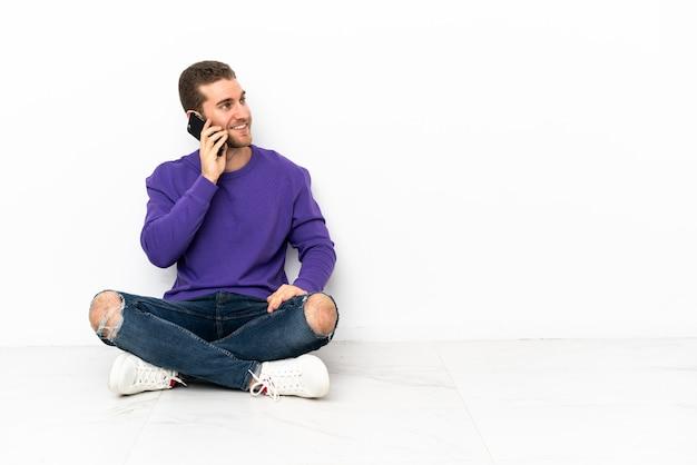 Giovane seduto sul pavimento che tiene una conversazione con il cellulare con qualcuno