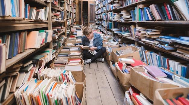Giovane uomo seduto sul pavimento in una vecchia biblioteca pubblica e libri di lettura.