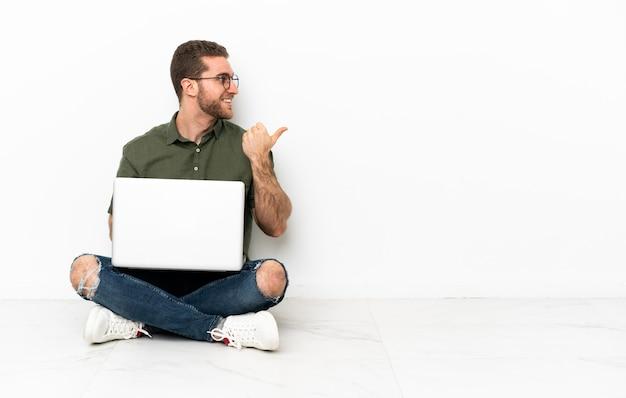Giovane uomo seduto sul pavimento che indica di lato per presentare un prodotto