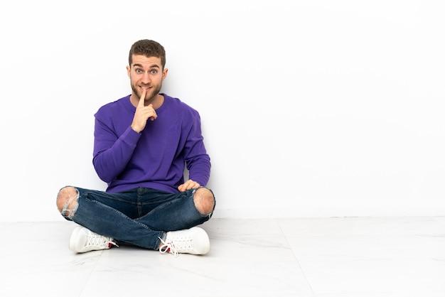 Giovane uomo seduto sul pavimento che mostra un segno di gesto di silenzio mettendo il dito in bocca