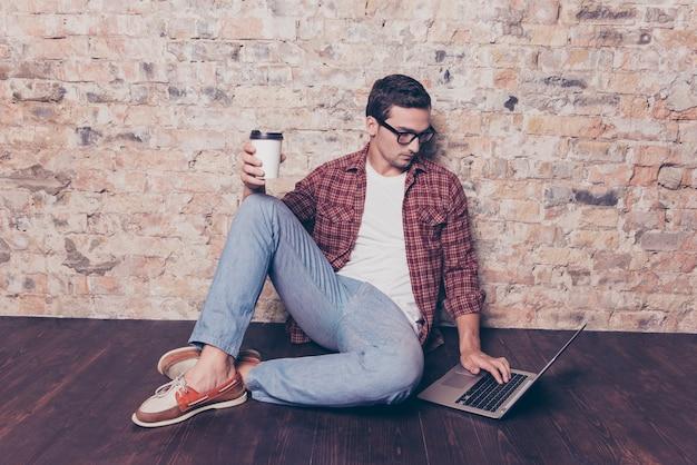 Giovane uomo seduto sul pavimento con una tazza di caffè e laptop