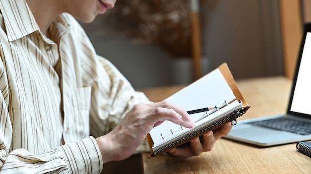 Giovane che si siede davanti al suo computer portatile e controlla le informazioni sul taccuino.