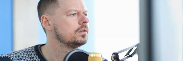 Giovane che si siede davanti al microfono in studio di registrazione. lavora come un conduttore radiofonico concept