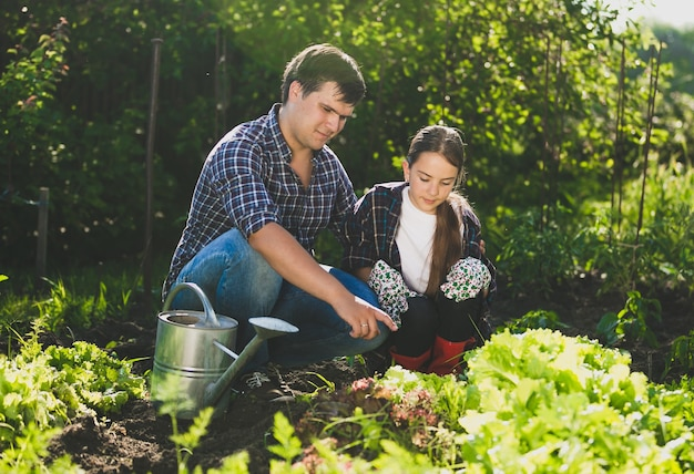Giovane uomo seduto in giardino con la figlia e insegnandole l'orticoltura