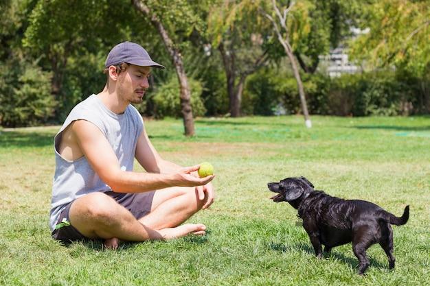 Giovane uomo seduto sull'erba che mostra la pallina da tennis al cagnolino nero proprietario maschio che gioca con l'animale domestico