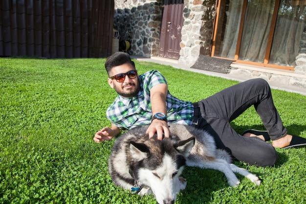 Giovane che si siede al prato verde e si diverte con il suo cane