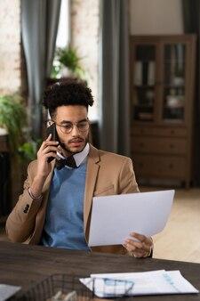 Giovane uomo seduto al suo posto di lavoro che parla al telefono cellulare ed esamina il contratto d'affari in ufficio