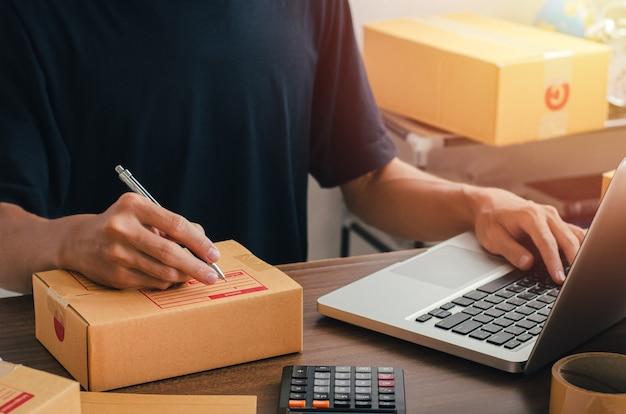 Giovane seduto a casa imballaggio da inviare per posta pronto a scrivere l'indirizzo di contatto del cliente dal taccuino per inviare la destinazione.