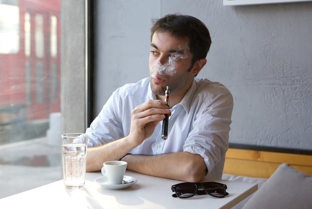 Giovane che si siede al chiuso che fuma sigaretta elettrica
