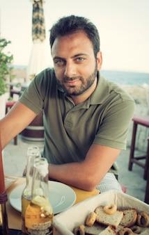 Giovane uomo seduto al ristorante vicino al mare.