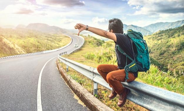 Giovane uomo seduto sul ciglio della strada. concetti di viaggio e vacanze. zaino in spalla su strada. uomo di viaggio autostop