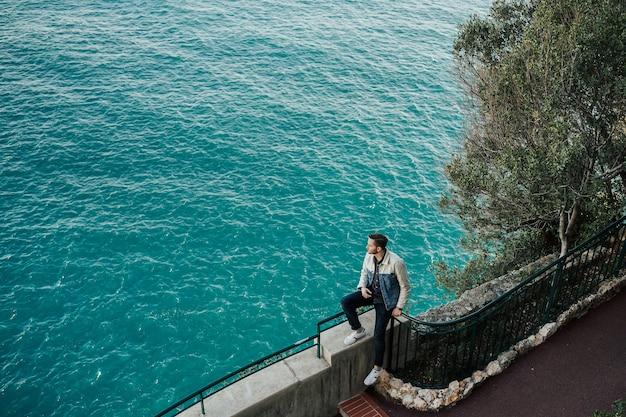 Giovane uomo seduto sul lungomare in abiti eleganti a monaco, sulla costa azzurra.