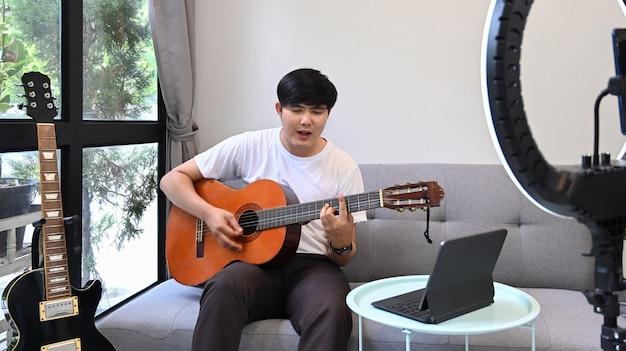 Giovane uomo seduto sul divano e suonare la chitarra in streaming vlog online a casa.