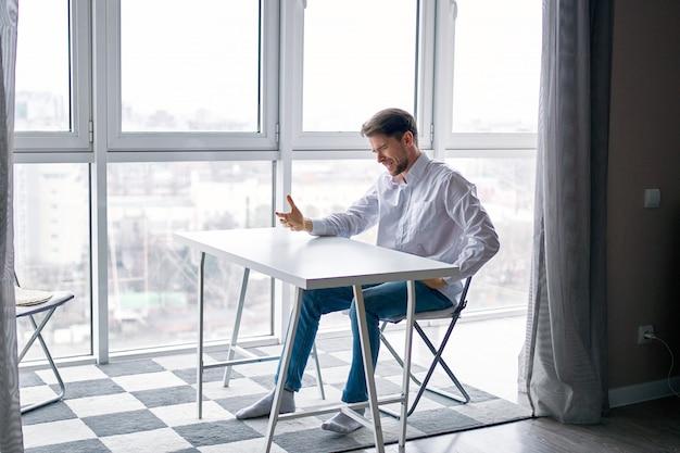 Giovane uomo seduto a un tavolo depresso contro una finestra