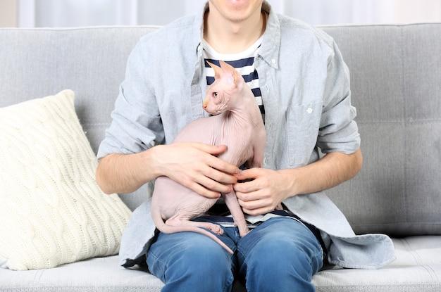 Giovane uomo seduto con il gatto sul divano di casa