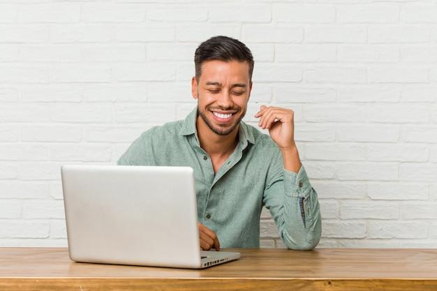 Lavoro di seduta del giovane con il suo computer portatile allegra che ride molto