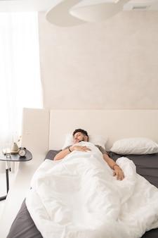 Giovane che dorme pacificamente sotto una coperta bianca in un grande e comodo letto matrimoniale davanti a un tavolino con sveglia e altre cose