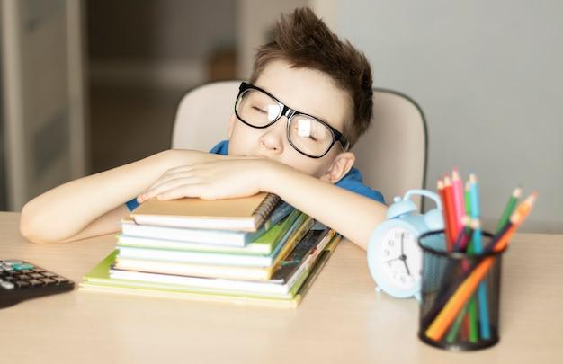 Giovane che dorme con i libri al tavolo in camera