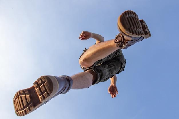 Giovane uomo in camicia a maniche corte e pantaloni cargo corti in piedi nel parco