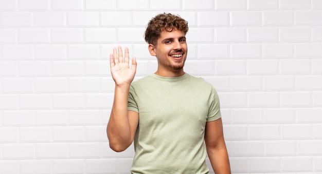 Giovane che sorride allegramente e allegramente, agitando la mano, dandoti il benvenuto e salutandoti o salutandoti