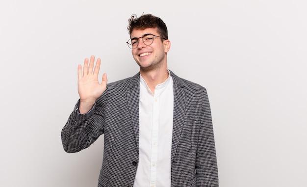 Giovane che sorride allegramente e allegramente, agitando la mano, accogliendoti e salutandoti o salutandoti