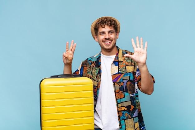 Giovane uomo sorridente e guardando amichevole, mostrando il numero otto o ottavo con la mano in avanti, il conto alla rovescia. concetto di vacanze