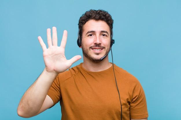 Giovane che sorride e sembra amichevole, mostrando il numero cinque o quinto con la mano in avanti, conto alla rovescia