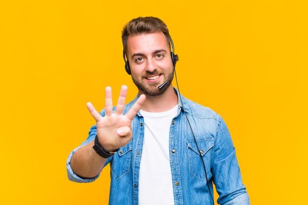 Giovane che sorride e sembra amichevole, mostrando il numero quattro o quarto con la mano in avanti, contando alla rovescia