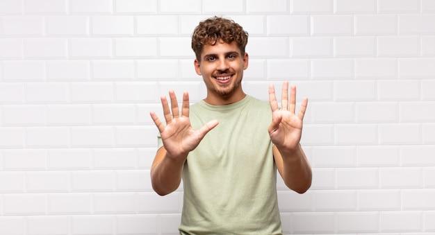 Giovane uomo sorridente e guardando amichevole, mostrando il numero nove o nono con la mano in avanti, il conto alla rovescia