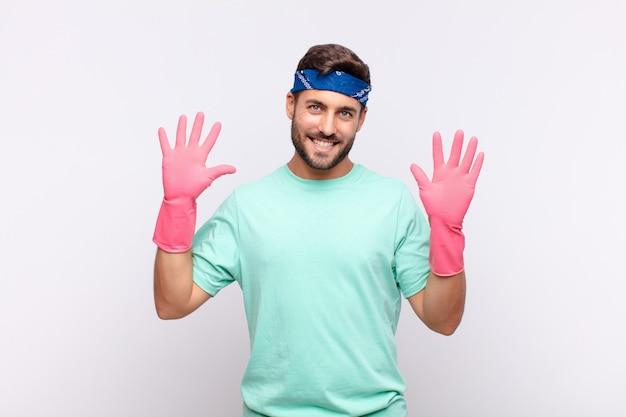 Giovane che sorride e sembra amichevole, mostrando il numero dieci o decimo con la mano in avanti