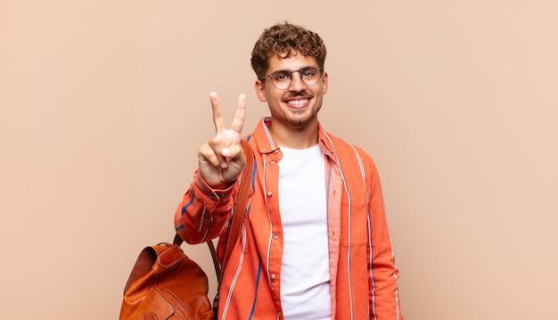 Giovane che sorride e sembra amichevole, mostrando il numero due o il secondo con la mano in avanti, contando alla rovescia. concetto di studente