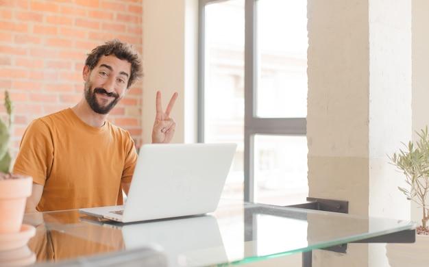 Giovane che sorride e che sembra felice vittoria gesticolante spensierata e positiva o pace con una mano