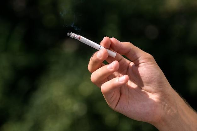 Giovane uomo che fuma sigaretta, inalazione di fumo di tabacco tossico, fumo uccide, avvertimento