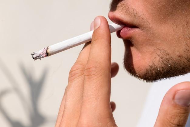 Giovane che fuma sigaretta, inalando fumo di tabacco tossico.