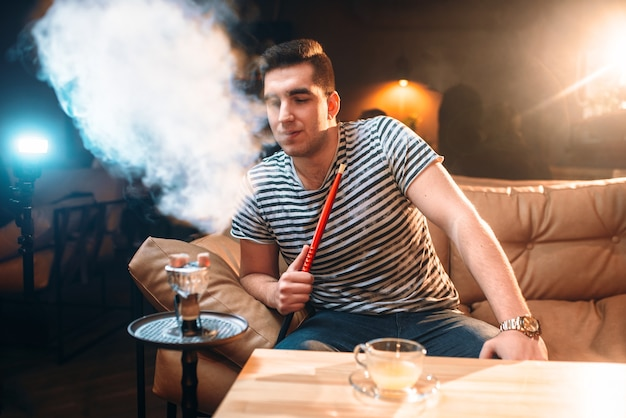 Giovane uomo che fuma e relax al bar narghilè