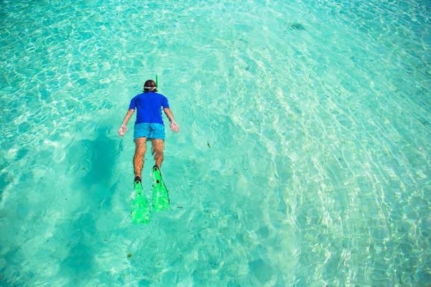 Giovane uomo lo snorkeling in acque turchesi tropicali chiare