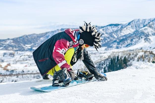 Lo snowboarder del giovane in cappello di fanny si siede nella neve e fissa i fissaggi su uno snowboard