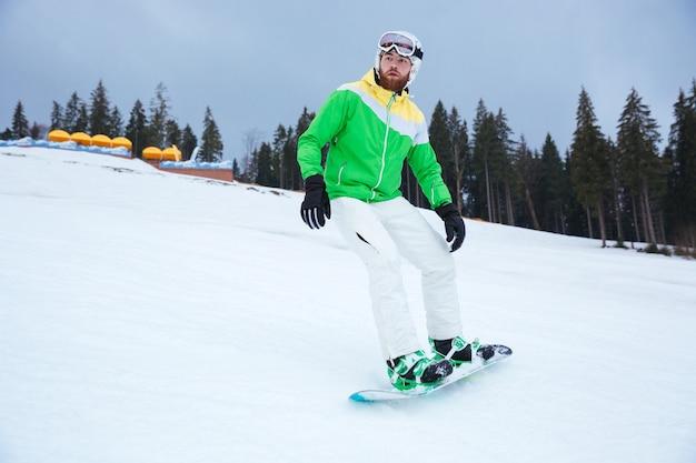 Giovane snowboarder sulle piste gelida giornata invernale