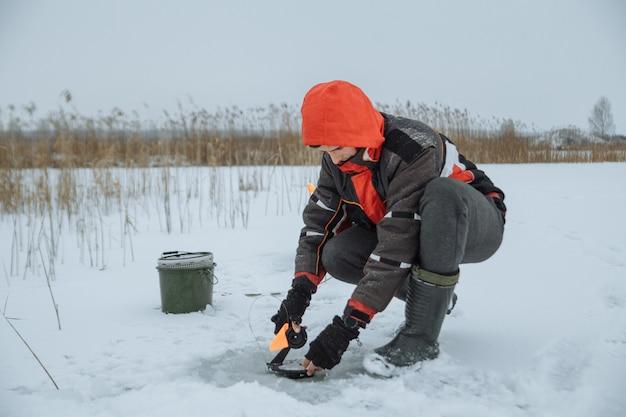 Il giovane su un pescatore di inverno del lago nevoso mette l'esca