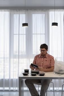 Giovane uomo che ordina le scatole di consegna degli alimenti nella cucina moderna Foto Premium