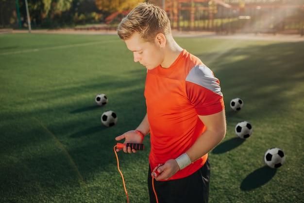 Il giovane in uniforme sportiva è pronto per l'esercizio con la corda per saltare. lui guarda in basso. guy stare sul prato verde. cinque palloni da calcio sono dietro.