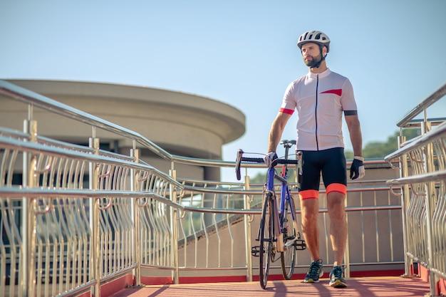 Giovane uomo in abiti sportivi con una bicicletta