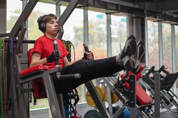 Giovane uomo in abiti sportivi e cuffie scuote la stampa in palestra