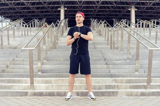 Giovane uomo in abbigliamento sportivo. l'uomo urbano si prepara a fare jogging in città. allenarsi urbano