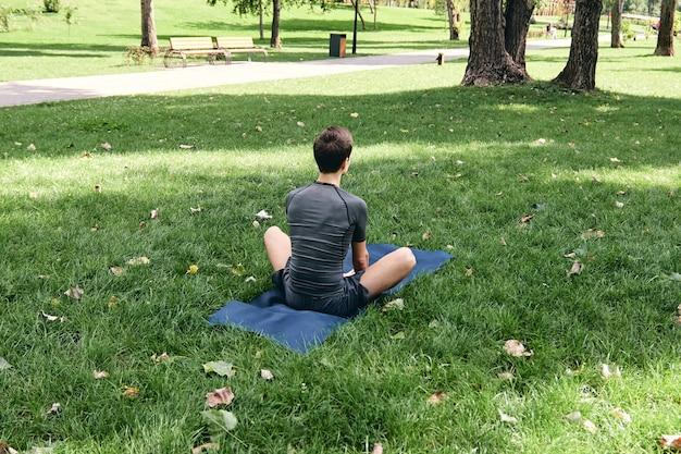 Giovane in abiti sportivi che fa yoga nel parco. pratica le asana all'aperto. esercitandosi sull'erba verde sulla stuoia di yoga. uomo seduto nella posa del loto farfalla, calma e meditazione. fitness e stile di vita sano