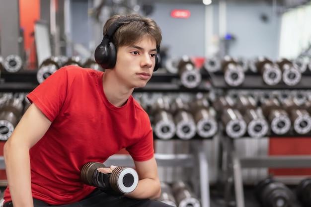 Giovane uomo in abbigliamento sportivo e cuffie lavora con manubri in palestra