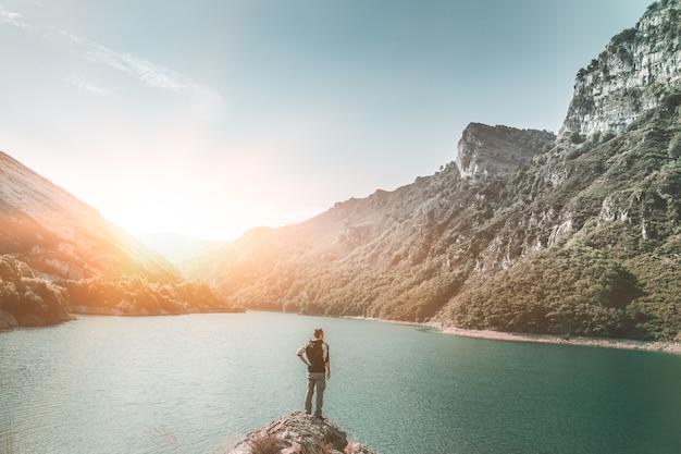 Giovane uomo in piedi in un fantastico paesaggio lacustre durante il tramonto uomo sognatore